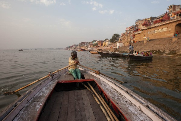 A man rowing his boat at Ganges River in Varanasi, India.