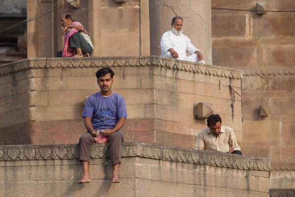 Man sitting at the banks of Ganges River in Varanasi, India.