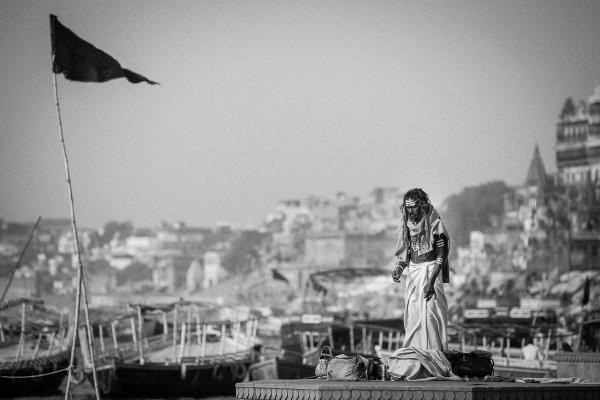 A man praying at the banks of Ganges River in Varanasi, India.