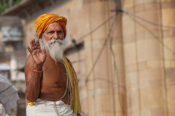 A man with an orange cover at the banks of Ganges River in Varanasi, India.