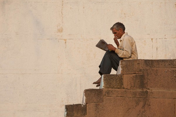 A man reading a book at the banks of Ganges River in Varanasi, India.