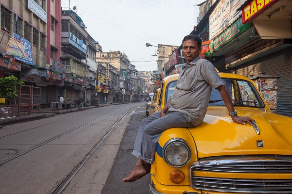 A taxi driver sitting on the hood of his yellow Ambassador Taxi.
