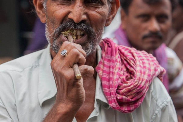 A man brushing his teeth at the street of Kolkata, India