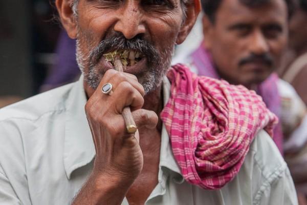 A man brushing his teeth at the street of Kolkata, India