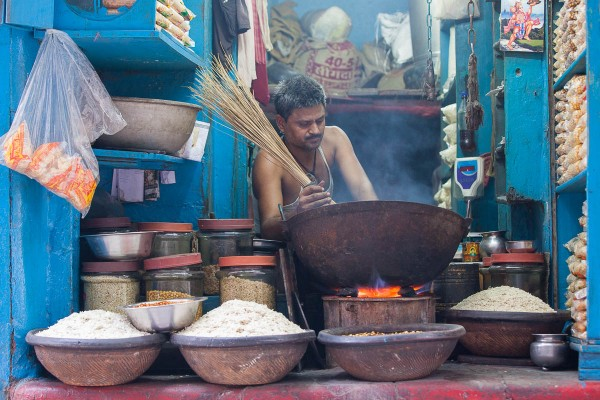 A man preparing dinner at a small shop by the main market street in Kolkata, India.