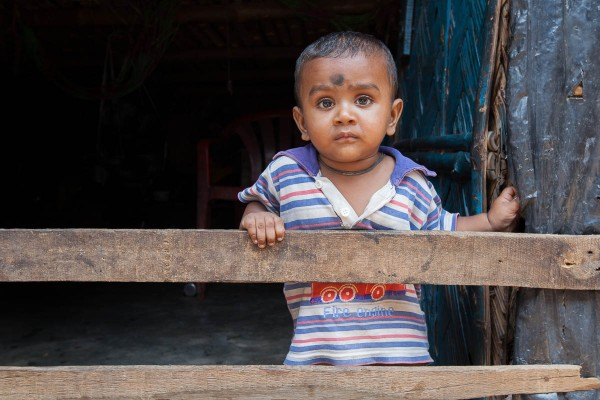 A child behind a fence in his house at one of the slums in Kolkata, India