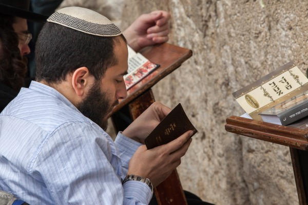 A jewish man praying in front of the Western Wall in Jerusalem, Israel