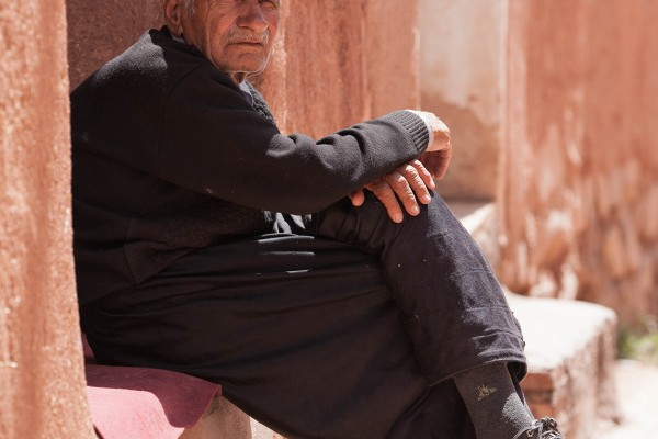 An old man sitting in front of his house in Abyaneh, Iran