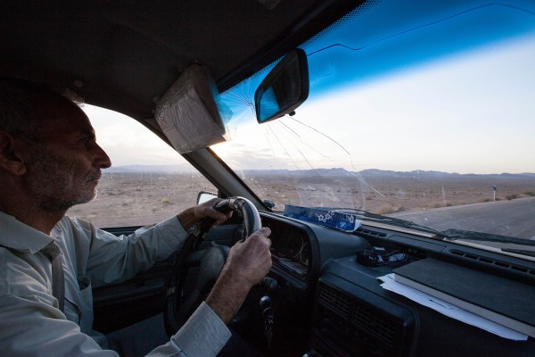 A taxi driver driving through the Dasht-e Kavir desert, Iran.