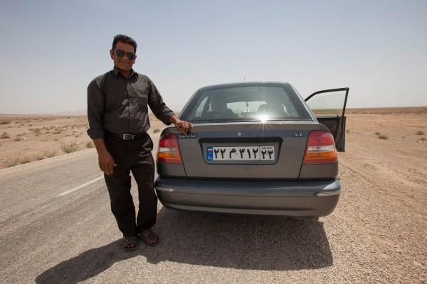 An iranian taxi driver posing in front of his car in Iran.