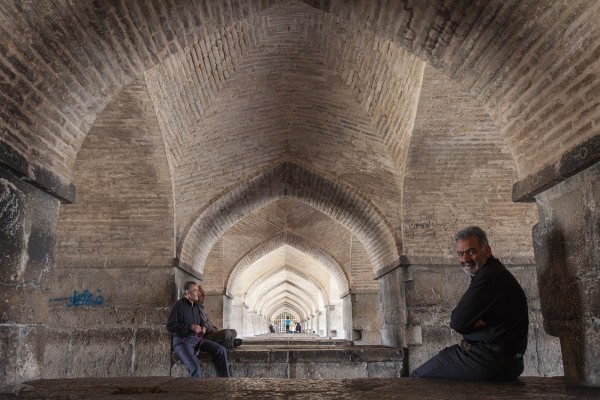 Couple of guys sitting under the Allah Verdi Khaan bridge in Esfahan, Iran