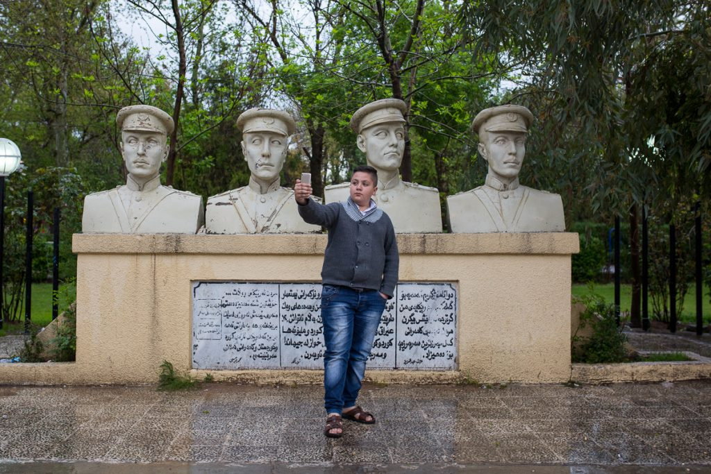 A younger man posing in front of statues in Sulaymaniyah, Iraqi Kurdistan