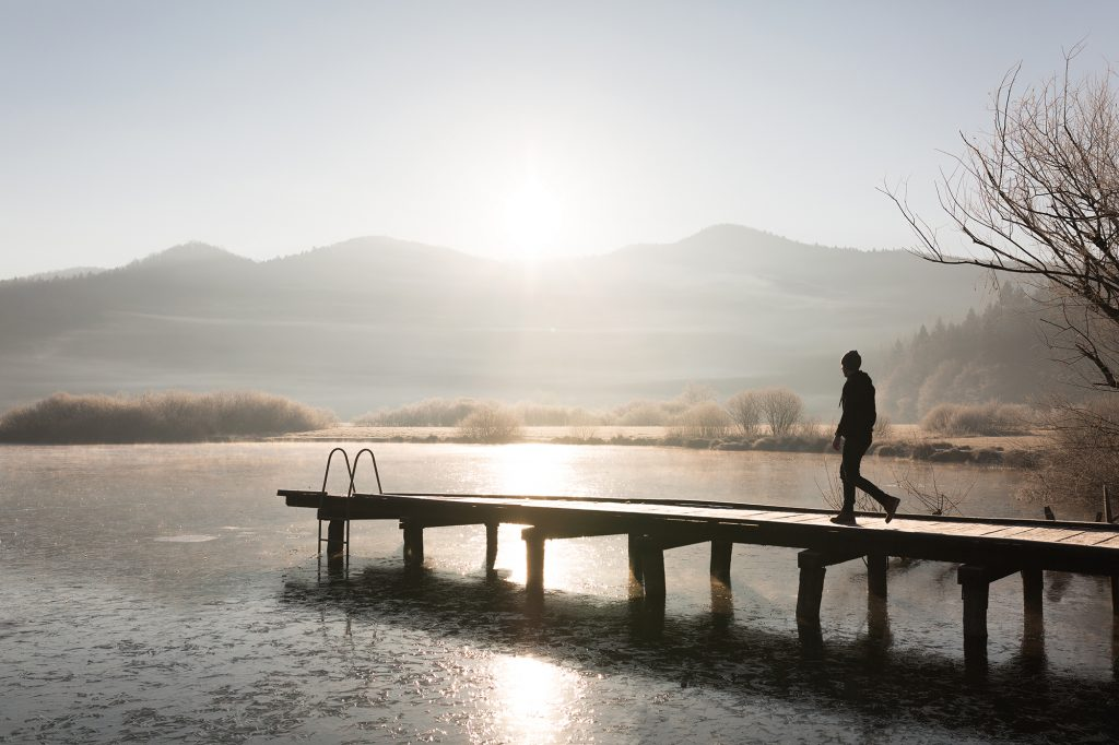 A man walking down a pier at Lake Podpeč, Slovenia.
