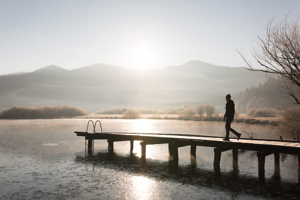 A man walking down a pier at Lake Podpeč, Slovenia.