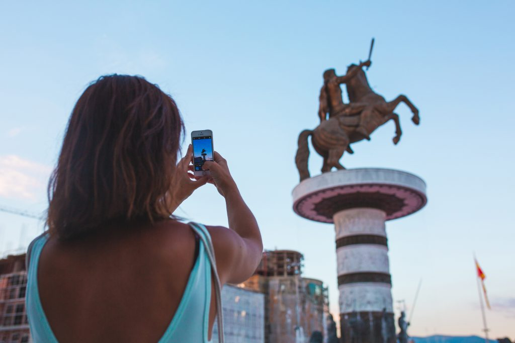 A girl making a photo with an Apple iPhone at Macedonia Square in Skopje, Macedonia
