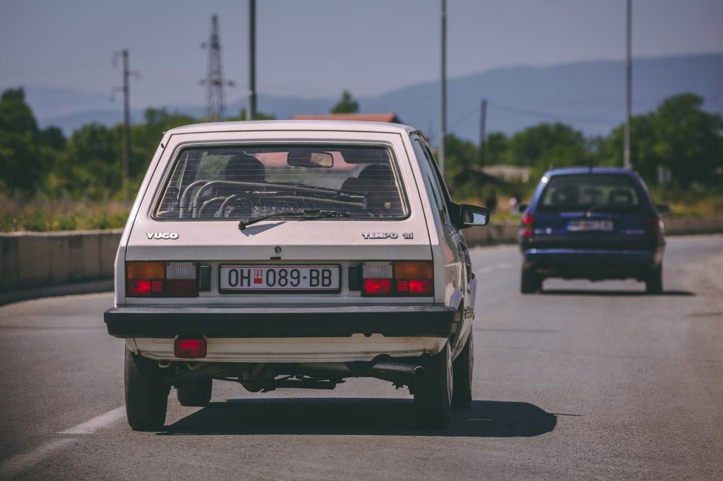 A YUGO driving on the street.