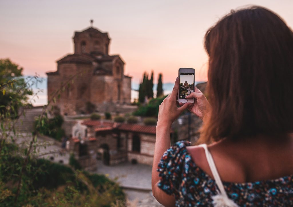 A girl photographing Church of St. John at Kaneo in Ohrid / Macedonia.
