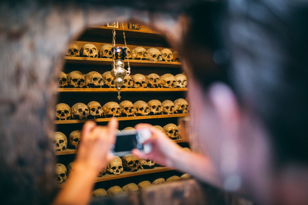 A girl photographing room full of Skulls in Great Meteoron Monastery in Meteora, Greece