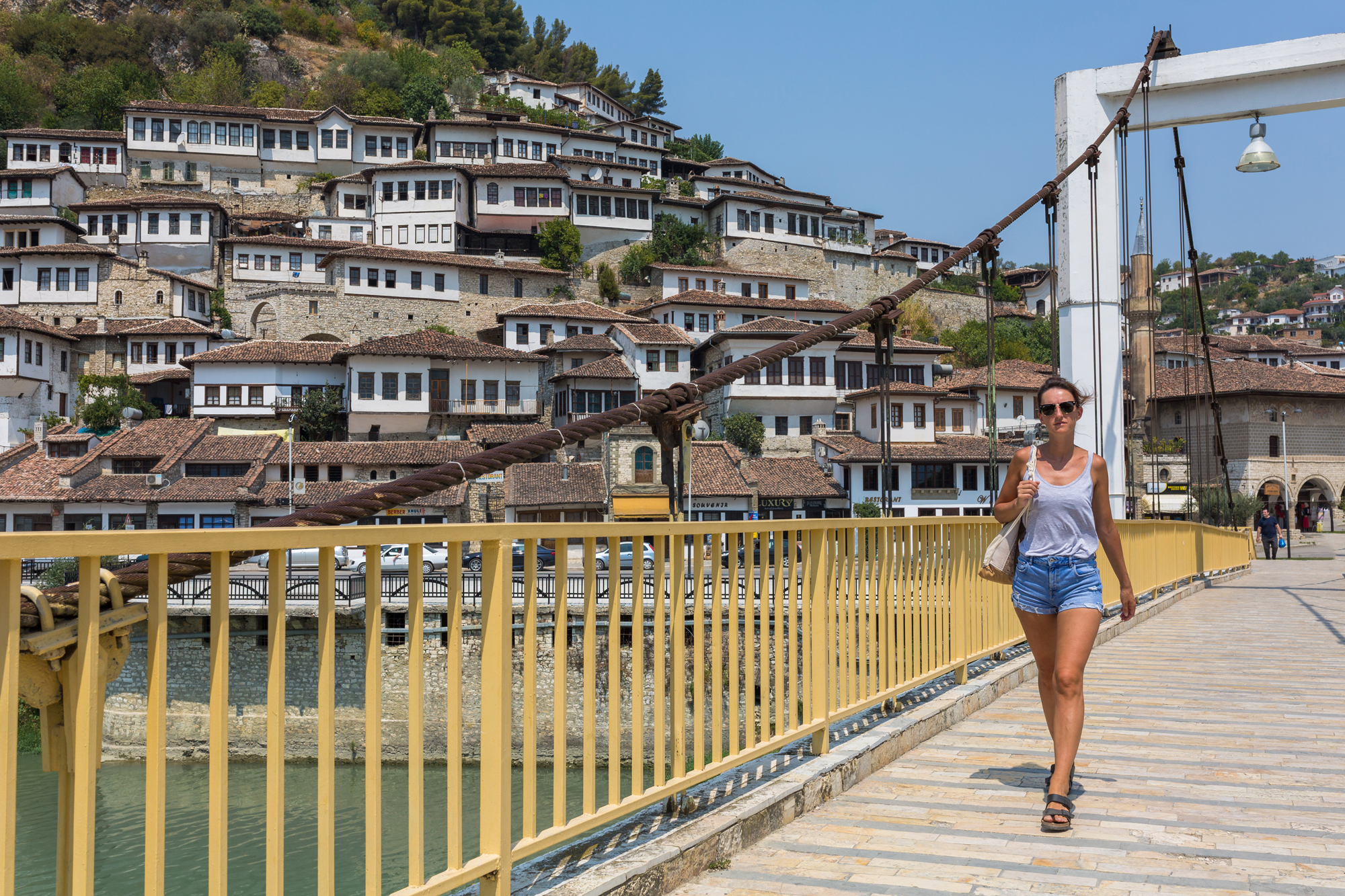 A girl walking across the bridge in Albania.