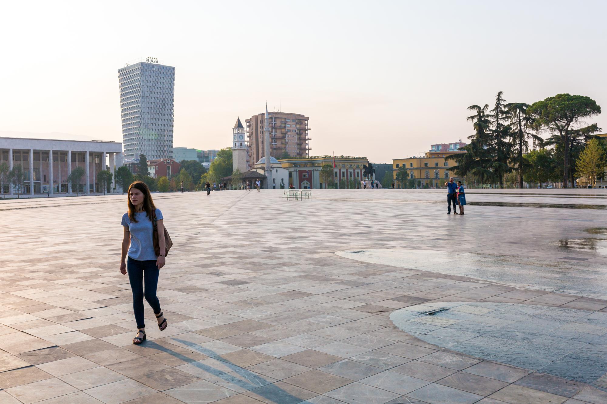 A girl walking across the main square in Tirana, Albania.