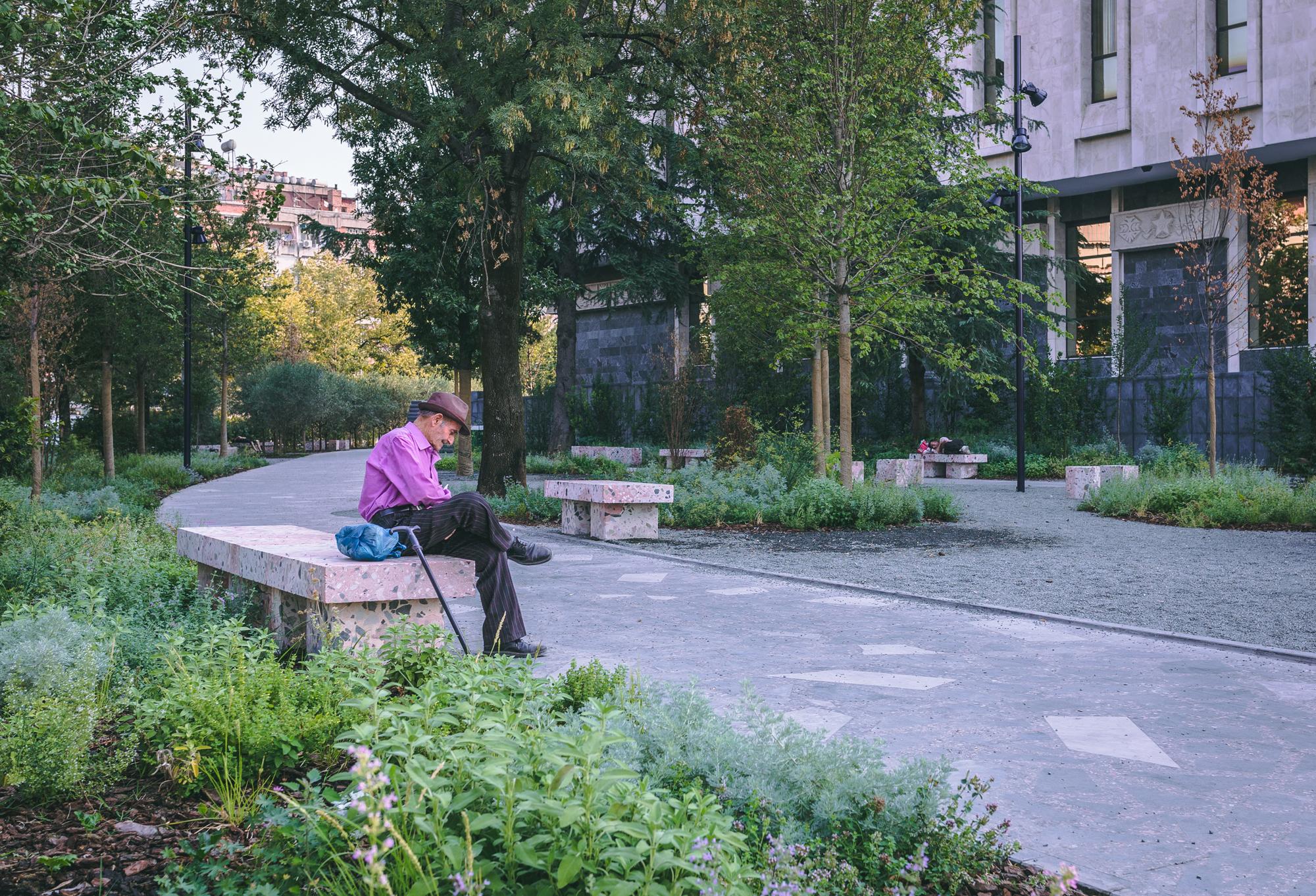 A man sitting on a bench in Tirana, Albania.